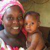 Kadia, responsable du centre ASHED d'accueil d'enfants au Mali, tient un jeune enfant dans ses bras et nous sourit