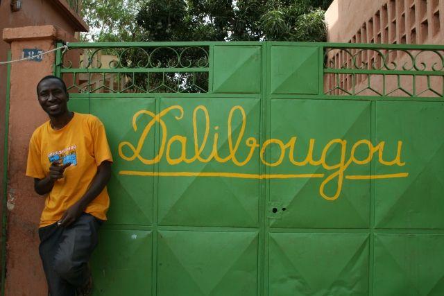 Mamadou Toure pose devant l'entrée du centre SInjiaTon
