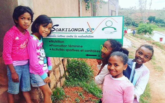 Enfants malgaches qui sourient à l'entrée d'un centre de nutrition de l'association Soakilonga