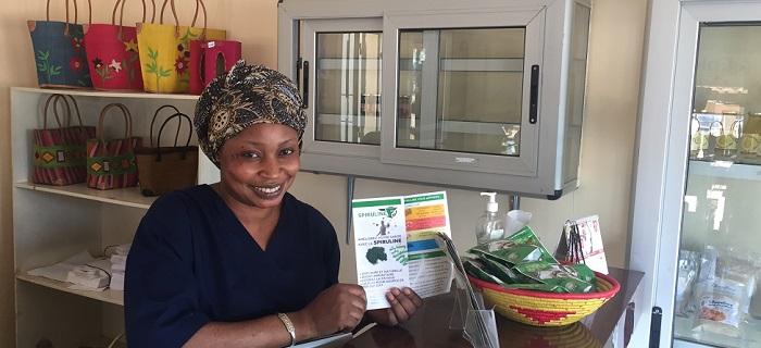 Femme qui vend de la spiruline dans une boutique de bamako au Mali et montre un dépliant