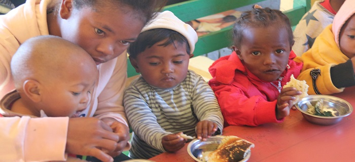 maman qui aide des enfants à manger un repas avec spiruline - madagascar
