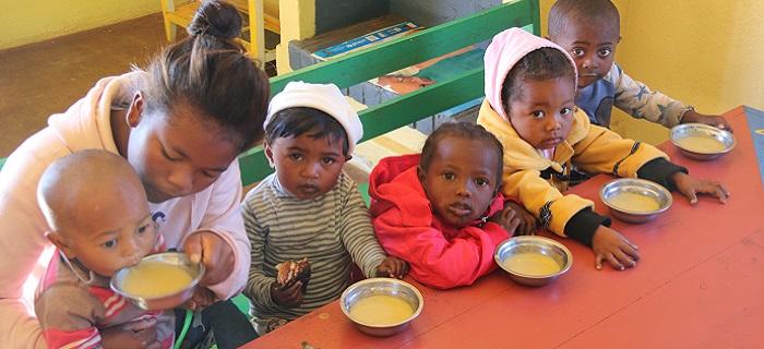 maman malgache qui aide des enfants à prendre leur repas - Madagascar