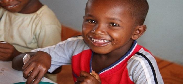 Enfant malgcache en train de manger avec le sourire - cantine scolaire de l'association Esperanza Joie des Enfants à Madagascar